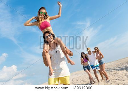 Full of joy. Cheerful handsome man holding his girlfriend on the shoulders and resting on the beach while their friends standing in the background