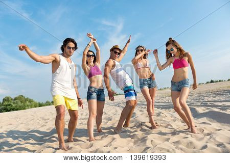 Rise your mood. Cheerful jubilant smiling friends standing on the sand and feeling glad while having fun on the beach