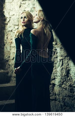young pretty women with long lush curly blonde hair and thoughtful face in green dress standing near stony wall