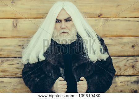 Druid old man with long grey hair and beard on serious face outdoor on wooden background in fur coat
