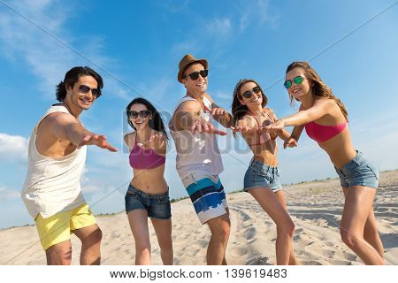 Share our emotions. Positive delighted smiling friends standing on the beach and holding hands in front of them while resting together