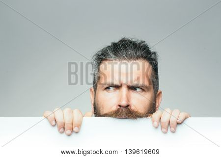 young man with sad face with long hair behind white paper sheet in studio on grey background copy space