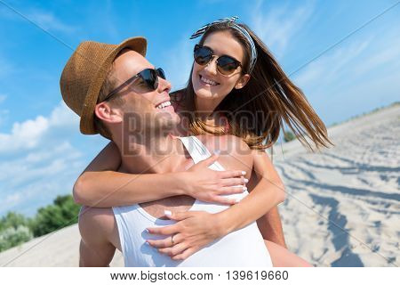 Happy with you. Cheerful handsome smiling man holding his girlfriend on the back and expressing joy while resting together on the beach