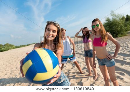Play with us. Close up of ball in hands of pleasant delighted beautiful woman holding it and going to play volleyball while having fun with her friends on the beach