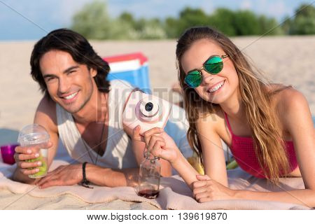 Pleasant relaxation. Cheerful joyful friends smiling and resting on the beach while lying on the blanket