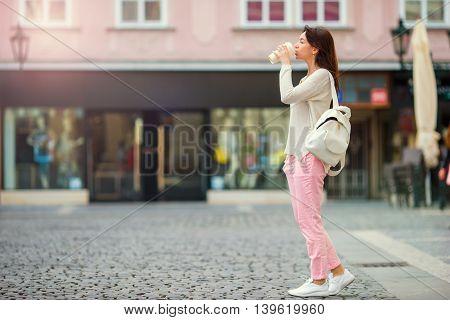 Girl caucasian drinking hot drink coffee walking in street at Europe