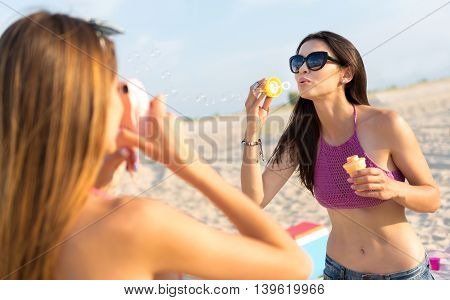 Positive memories. Cheerful beautiful delighted woman blowing soap bubbles while posing in front of the camera on the beach
