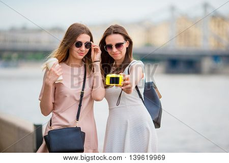 Happy tourist couple, two girlfriends traveling on holidays in Europe smiling happy. Caucasian women.