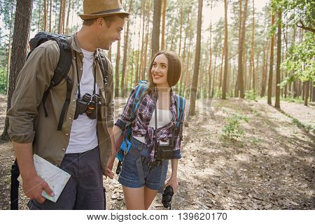 Joyful tourists are making travel in forest. They are holding hands and smiling. Man is looking at woman with love