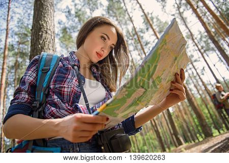 Young woman is trying to find the way through touristic map. She is standing with backpack in forest