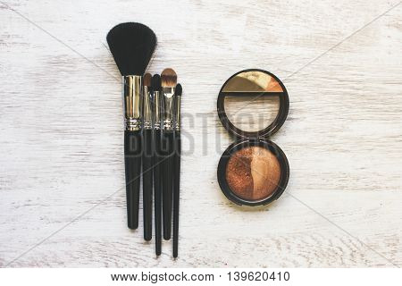 Brushes for cosmetics and powder are laid out on a white wooden table