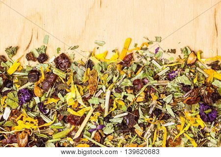 Border frame of assorted natural medical dried herb leaves and flower petals on wooden board with copy space