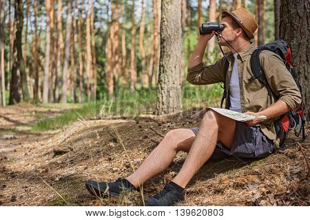 Young tourist is traveling in forest. He is sitting and looking into the binoculars with interest. Man is holding a map