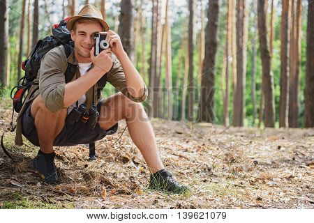 Cheerful male traveler is taking photos of forest. He is kneeling and smiling. Man is carrying backpack