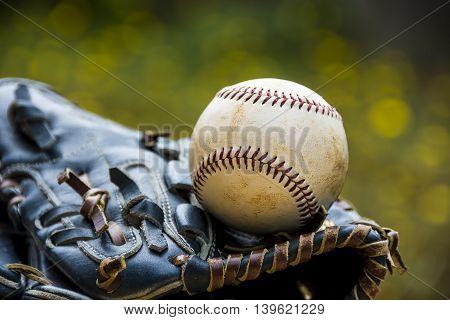 A worn baseball rests on a blue baseball glove.