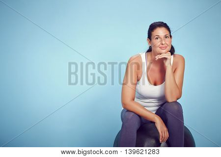Sitting Smiling Young Yoga Woman On Blue Background