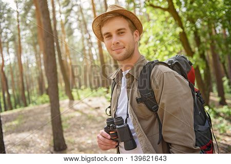 Joyful young traveler is resting in forest. He is standing and holding binoculars. Man is looking at camera and smiling