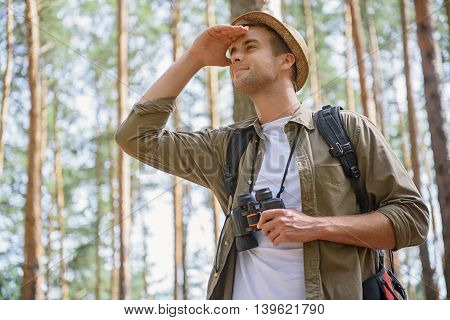 Young tourist is looking for location. He is standing and covering his eyes from sunshine. Man is holding binoculars and smiling