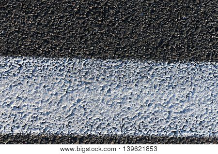 photographed close-up of the new road for the movement of vehicles, a dark cover the carriageway road markings - white stripes