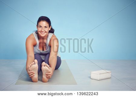 Smiling Young Yoga Woman Stretching Her Feet
