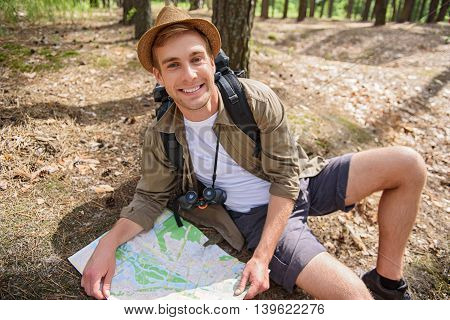 I found the way. Happy young man is making journey in forest. He is sitting on ground and holding map. Tourist is looking at camera and smiling
