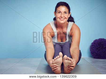 Smiling Young Yoga Woman Stretching On The Floor