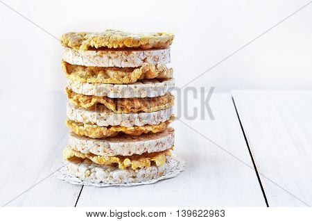 Round rice cakes and corn cakes on wooden table.