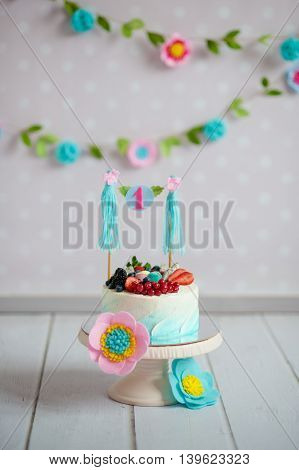 Birthday cake decorated with fruits and a garland with the inscription 1 on a support on a white wooden floor. A flower garland on the wall.