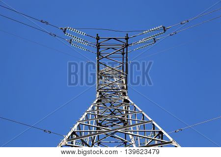 photographed close-up, high-voltage electric poles against the blue sky