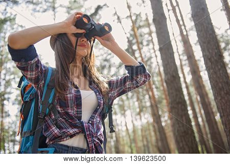 Skillful female tourist is looking into binoculars with interest. She is standing with backpack in forest. Woman is smiling