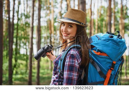 Carefree young woman is making touristic travel in forest. She is holding binoculars and smiling