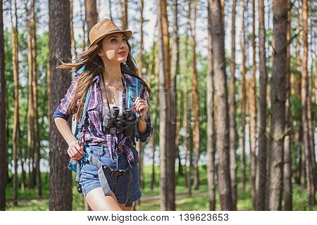 Cheerful young woman is walking in forest with backpack. She is looking around with enjoyment
