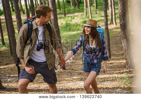 Cheerful man and woman are making touristic travel in nature. They are walking and smiling. Tourists are holding hands