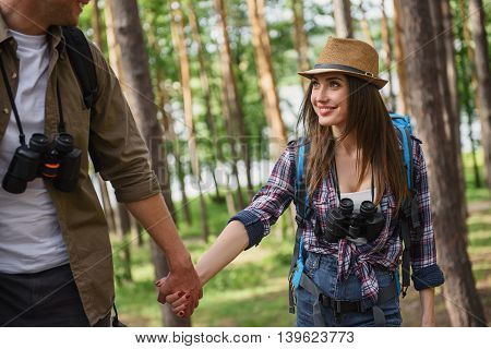 Happy loving couple is traveling in forest. They are holding hands and smiling