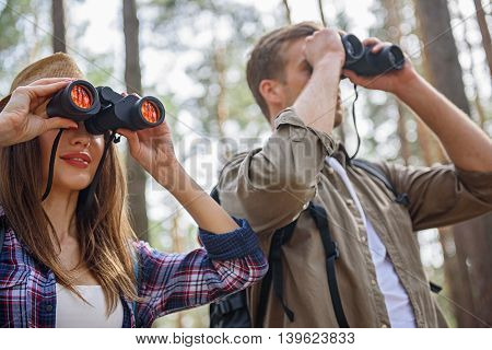 Joyful tourists are enjoying scenery in forest. They are standing and looking into binoculars. Woman is smiling