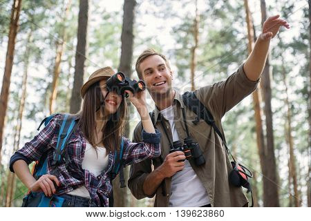 Happy loving couple is making journey in forest. Man is showing something and smiling. Woman is looking into binoculars with interest
