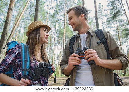 Carefree young tourists are enjoying romantic trip. They are looking at each other with love and smiling. Couple is standing and holding binoculars