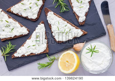 Pumpernickel bread with feta cream cheese rosemary lemon and garlic dip on slate board top view horizontal