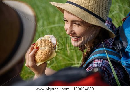 Carefree couple is making touristic picnic in meadow. Woman is looking at man and smiling. They are sitting on grass