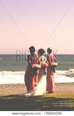 A bride and her bridesmaids face the ocean with their bouquets behind them