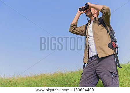 Cheerful man is looking for place of destination with seriousness. He is standing on grass and using binoculars. Traveler is carrying touristic rucksack