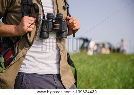Close up of male tourist standing on meadow. He is carrying backpack and binoculars. Car on background