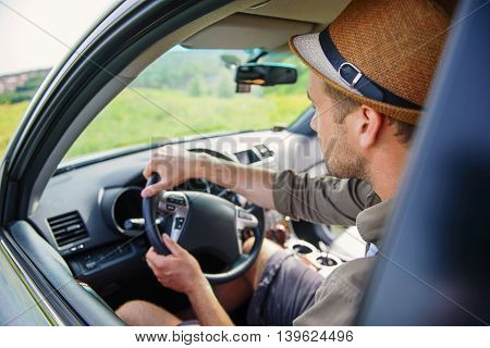 Young traveler is driving a car in countryside. Man is sitting and looking forward with seriousness