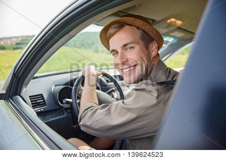 Happy male tourist is traveling by car in countryside. Man is sitting at steering wheel and smiling
