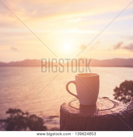 Coffee Cup At Sunset Or Sunrise Beach In The With Lens Flare. Warm Toning Effect. Retro And Vintage