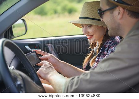 Happy loving couple is traveling by car on vacation. Man is showing mobile phone to his girlfriend. Woman is looking at map and smiling