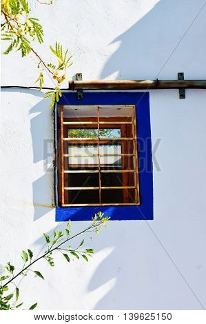 A blue window on a traditional white dwelling in Spain
