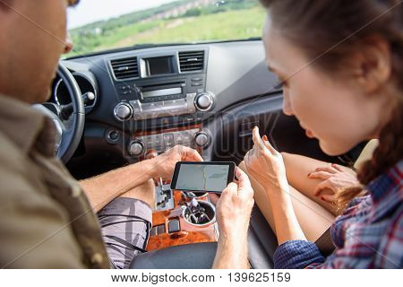 Young couple is looking for place of destination. They are looking at map in mobile phone with seriousness. Man and woman are sitting in car