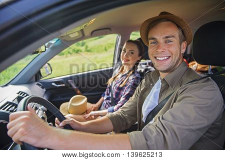 We like traveling. Joyful loving couple is sitting in car and smiling
