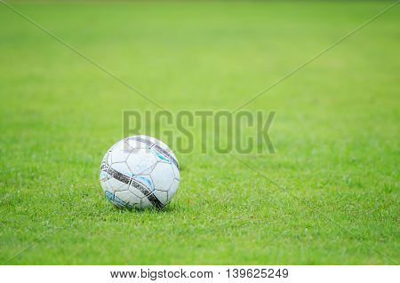 Soccer Ball On The Field And Blur Of Player In Stadium